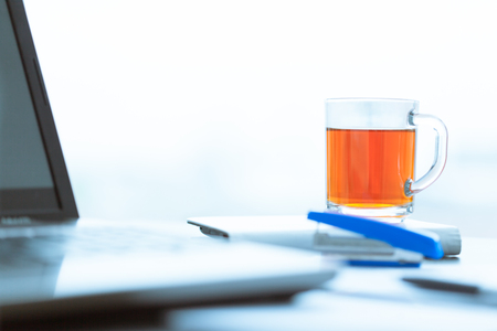 A cup of tea on a laptop. Studio shot Stock Photo