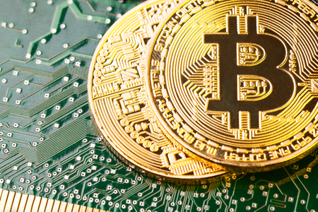 Golden Bitcoin Cryptocurrency on computer circuit board. Stock Photo