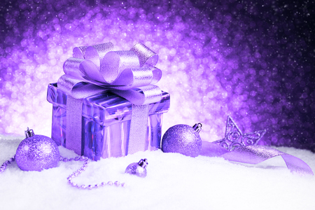 Christmas purple gift box with balls and star on snow