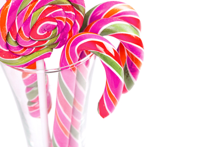 Glass with christmas candy canes on white background