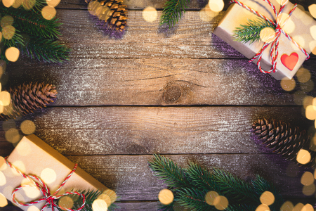 Christmas gifts boxes with fir branches on wooden background top view
