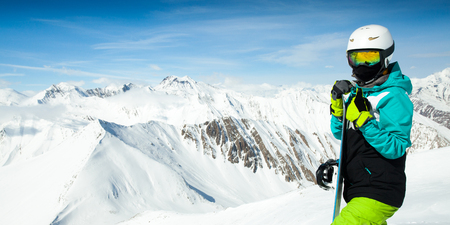 Portrait of snowboarder woman on background landscape of snowy high mountains Stock Photo