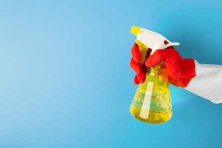 A hand in a red glove holds a spray of cleaning fluid Stock Photo