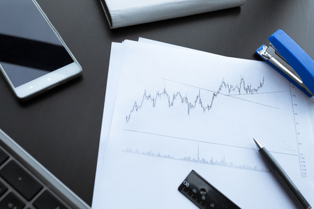 Investment charts with laptop. Accounting Stock Photo