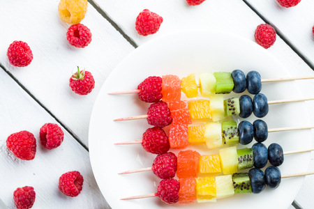 Coloerd fruits and berries kebab on wooden table