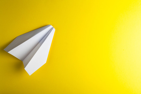 paper airplane on yellow background Stock Photo