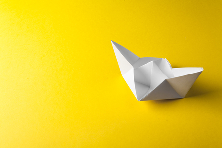 boat paper origami on the yellow background Stock Photo