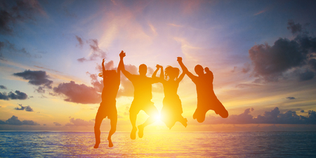 Silhouette of happy business team making high hands in sunset sky background Stock Photo