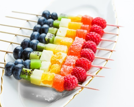 Fresh fruits on skewers in plate on table