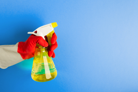 A hand in a red glove holds a spray of cleaning fluid on a blue background