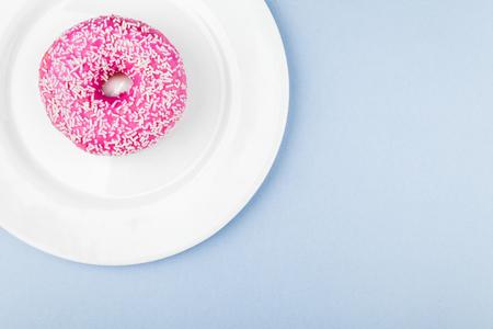 Pink glazed donut on blue pastel background