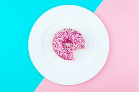 Minimalism, colour contrast on a blue and pink background, donut photo from above in flat style