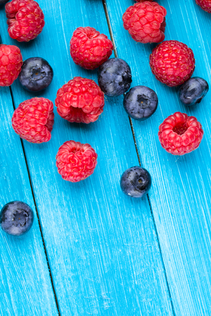 Blueberries and raspberries on blue wooden table Stock Photo