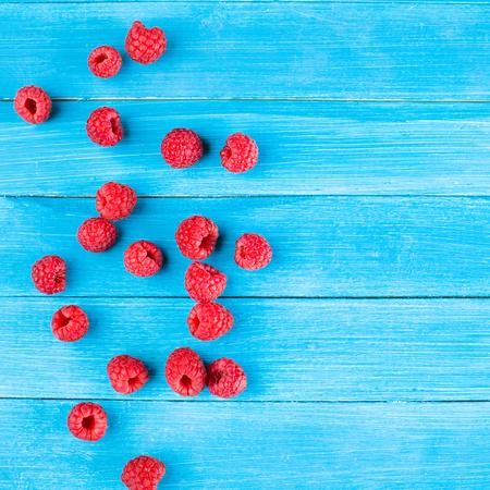 Raspberries on blue wooden table Stock Photo