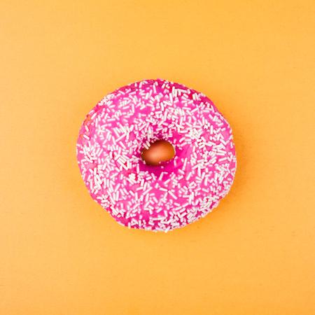 Pink glazed donut on orange background