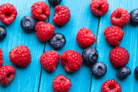 Blueberries and raspberries bowl on wooden table