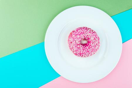 Pink glazed donut on color background