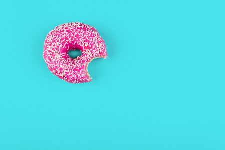 Minimalism, colour contrast on a blue background, donut photo from above in flat style Stock Photo