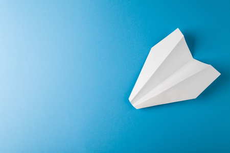 Paper airplane on a blue paper background Stock Photo