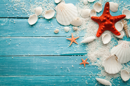 Marine items on sand on wooden background