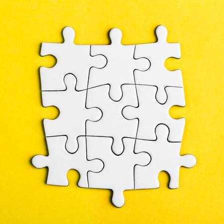 Connected blank puzzle pieces on a yellow background