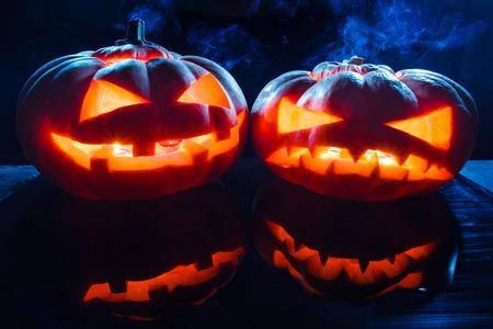 Two different Halloween pumpkins on dark background Stock Photo