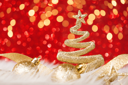 Shining Christmas tree with golden star and circle bokeh or glitter lights. Red festive background