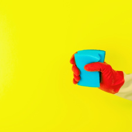 Cleaning with red rubber gloves and sponge on yellow background Stock Photo
