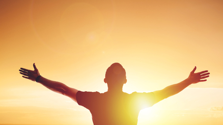 Young man standing outstretched at sunset. Bright solar glow and sky Stock Photo