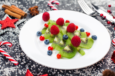 Kiwi christmas tree with raspberry, blueberry and cowberry on table with decoration