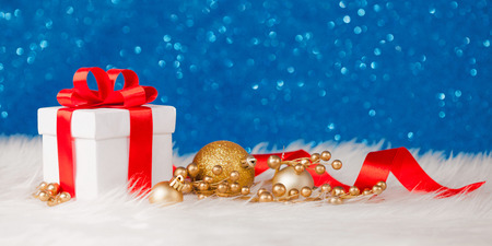 Christmas gift box or present with bow ribbon on magic turquoise bokeh background.