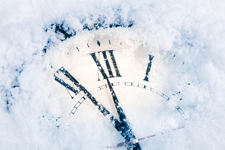 New Years clock in the snow. Christmas card Imagens