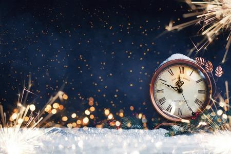 Zegar noworoczny. Ozdobiony kulkami, gwiazdą i drzewem na śniegu