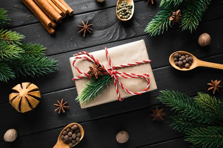 Vintage gift box with christmas decoration on dark wooden background.