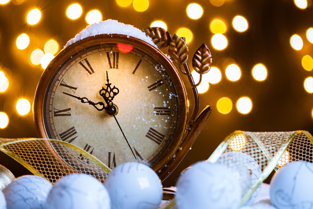 New Years clock and white balls covered with lights Stock Photo
