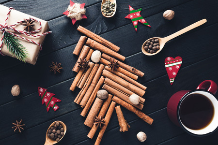 Christmas tree made of cinnamon, star anise, spices and nutmeg with decorations on dark background