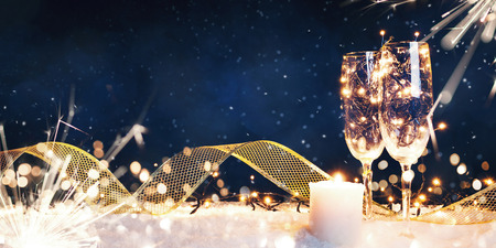 Two glasses filled with garlands with a candle and a gold ribbon in the snow
