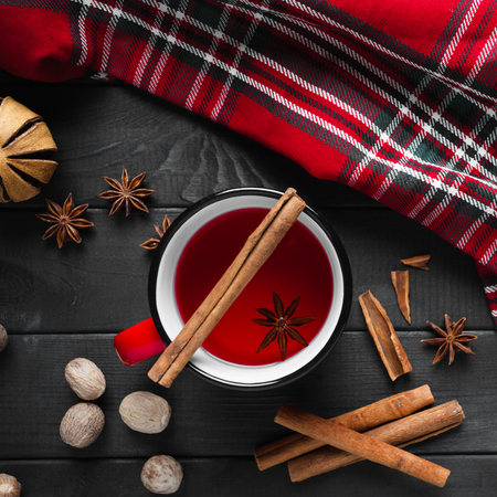 Christmas mulled wine with spices in red mug on wooden background.
