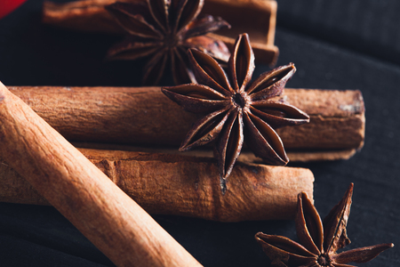 Anise star spices and cinnamon sticks on dark rystic wooden background Stock Photo