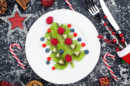 Edible christmas tree from kiwi slices on a black plate over dark slate, stone or concrete background