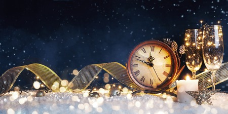 New Years clock with christmas decorations on snow