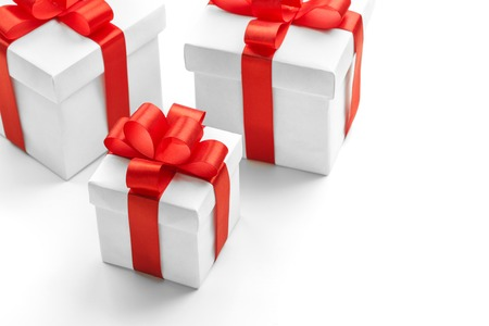 Three gift boxes with red ribbons on white background