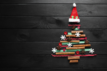 Tree made of christmas decoration on wooden dark background