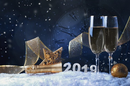 Glasses with champagne against vintage clock close to midnight