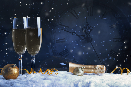 Two glasses of champagne with golden ribbon, star and ball with snow. Night of celebration concept Stockfoto