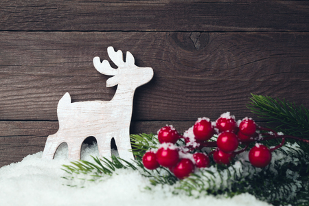 Christmas deer toy and tree on snow over wooden background