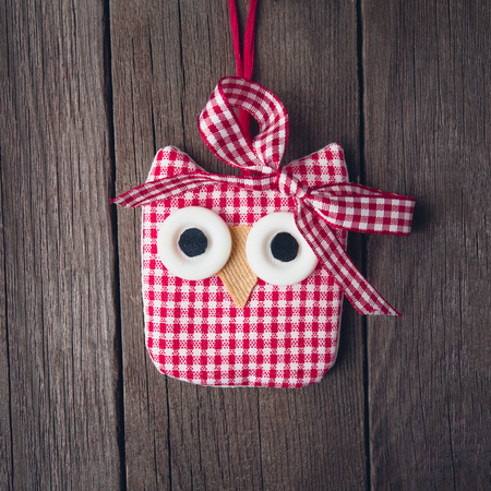 Owl toy with a bow on a wooden background