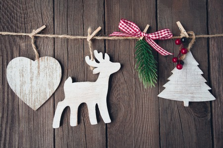 christmas wooden toys on string over wooden background