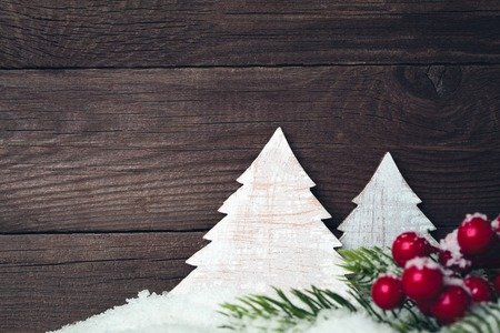 Two toy christmas trees in the snow on a wooden background