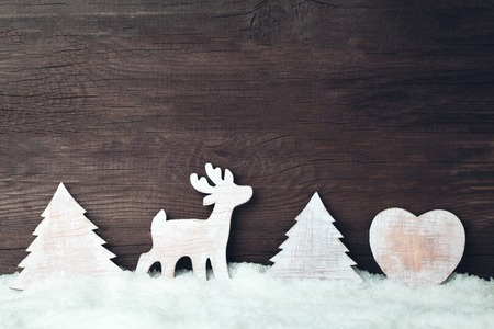 Christmas wooden toys in snow over a wooden background Stockfoto